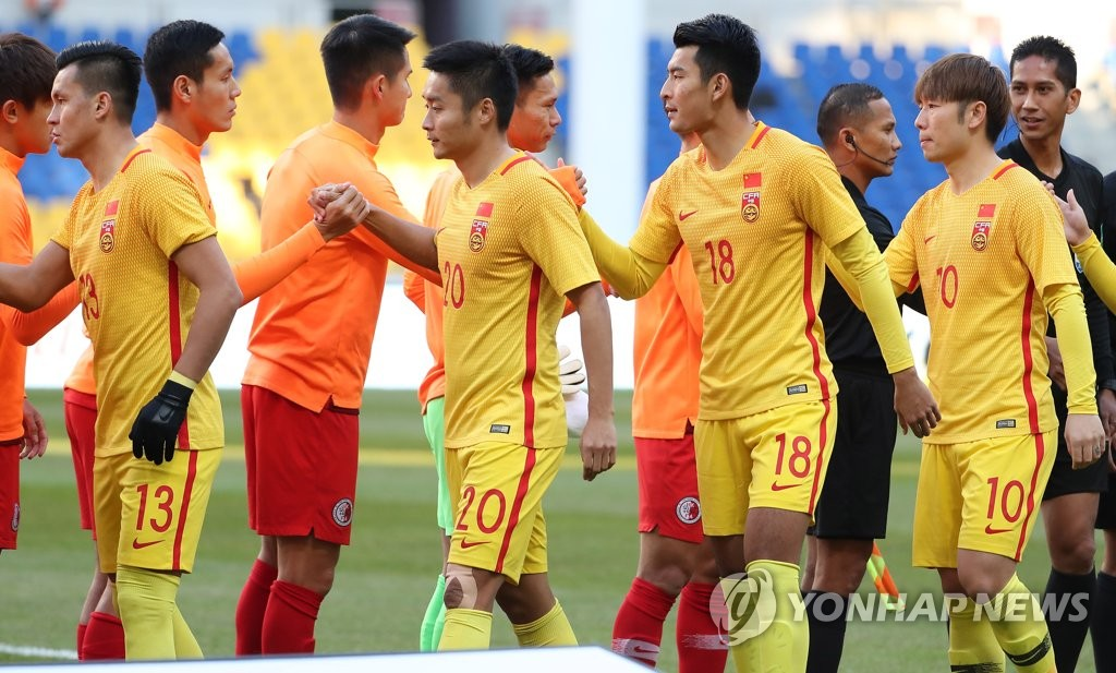 Players of the Chinese and Hong Kong men's national football teams shake hands before the start of their match at the East Asian Football Federation (EAFF) E-1 Football Championship at Busan Asiad Main Stadium in Busan, 450 kilometers southeast of Seoul, on Dec. 18, 2019. (Yonhap)