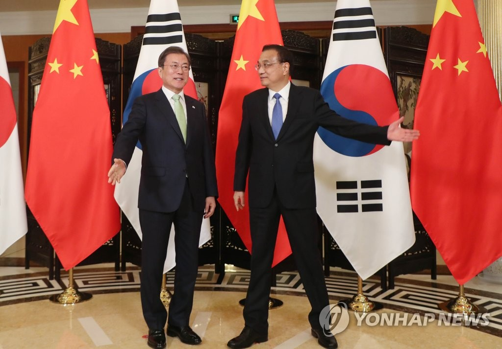 South Korean President Moon Jae-in (L) meets with Chinese Premier Li Keqiang at a hotel in Chengdu, Sichuan Province, on Dec. 23, 2019. (Yonhap)