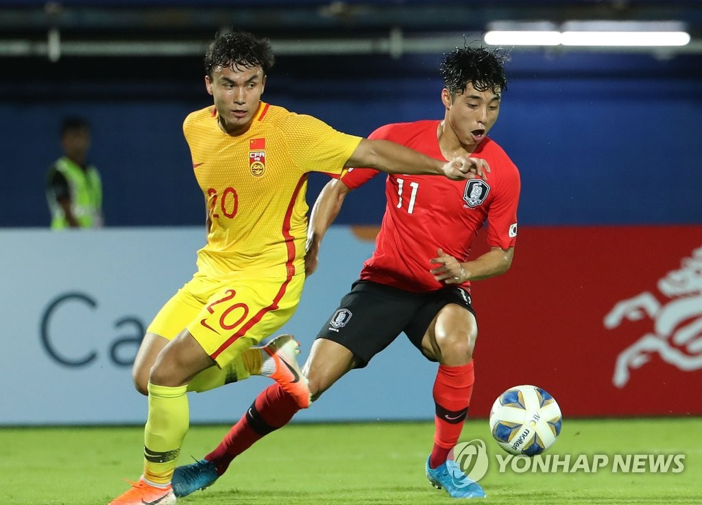 Lee Dong-jun of South Korea (R) tries to get past Dilmurat Mawlanyaz of China during the teams' Group C match at the Asian Football Confederation U-23 Championship at Tinsulanon Stadium in Songkhla, Thailand, on Jan. 9, 2020. (Yonhap)