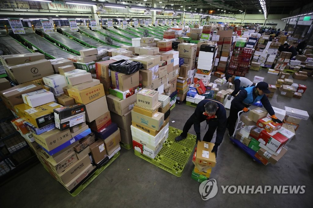 Workers at a logistics center affiliated with Korea Post in eastern Seoul sort deliveries on Jan. 14, 2020, ahead of the Lunar New Year holiday. (Yonhap)