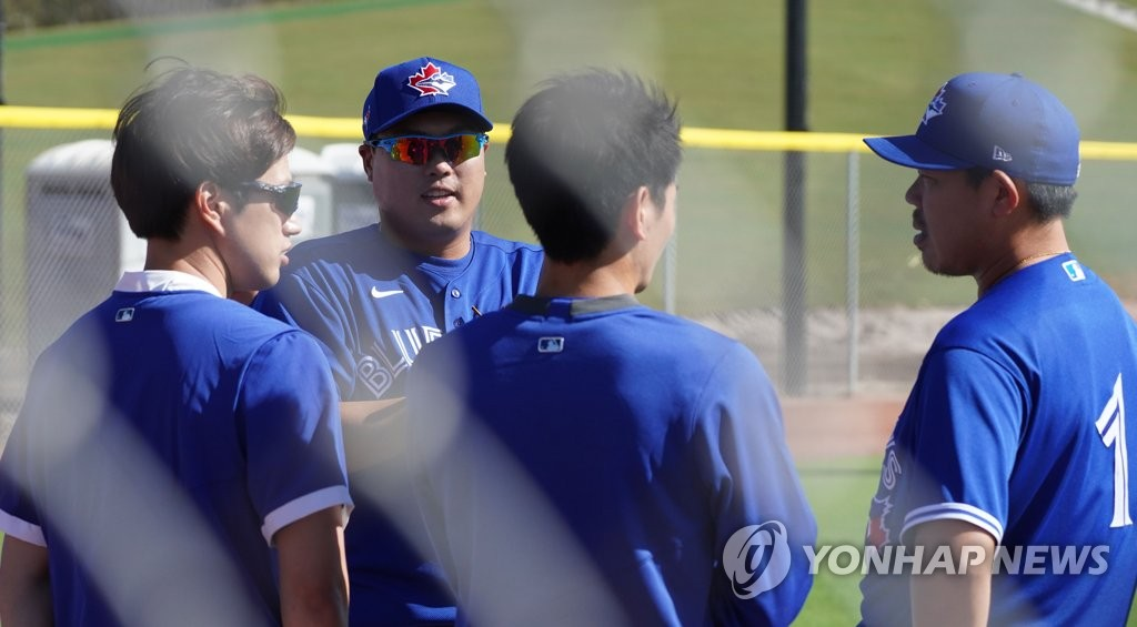 The Toronto Blue Jays' pitchers Ryu Hyun-jin (L) and Shun Yamaguchi (R) speak through their interpreters, Bryan Lee (2nd from L) and Yuto Sakurai (2nd from R), after their long toss at Player Development Complex, outside TD Ballpark, in Dunedin, Florida, on Feb. 15, 2020. (Yonhap)