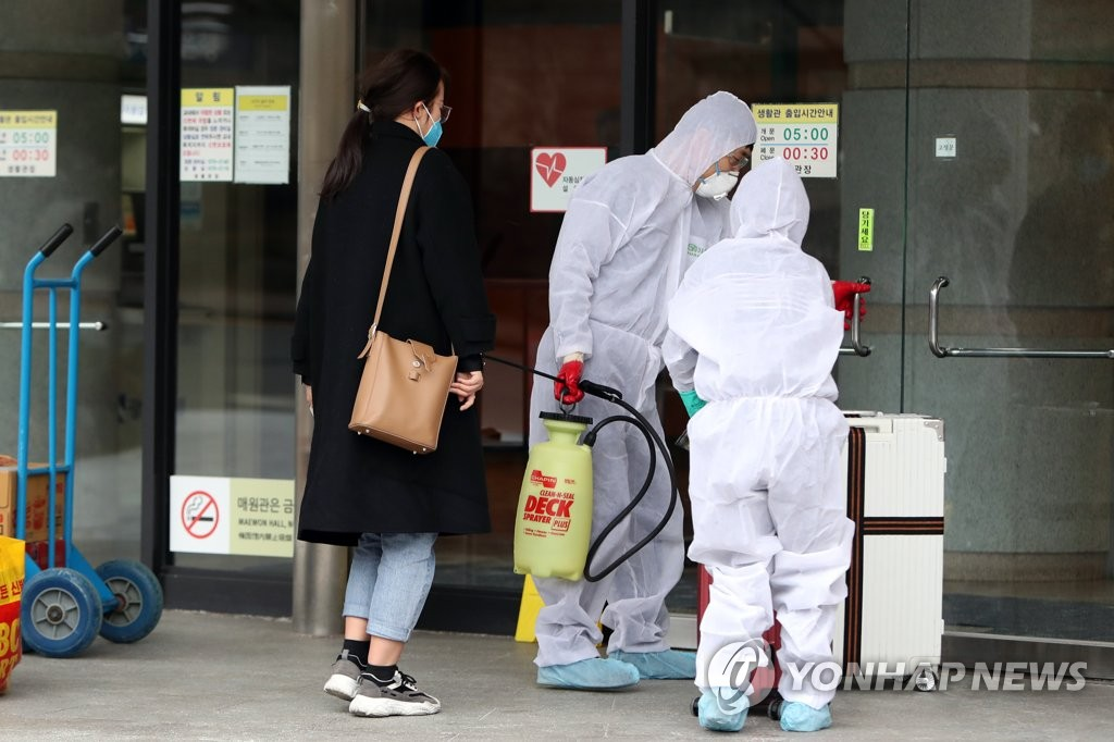 A Chinese student at Gwangju University in the southwestern city of Gwangju is helped by school officials before entering the dormitory on Feb. 28, 2020. (Yonhap)