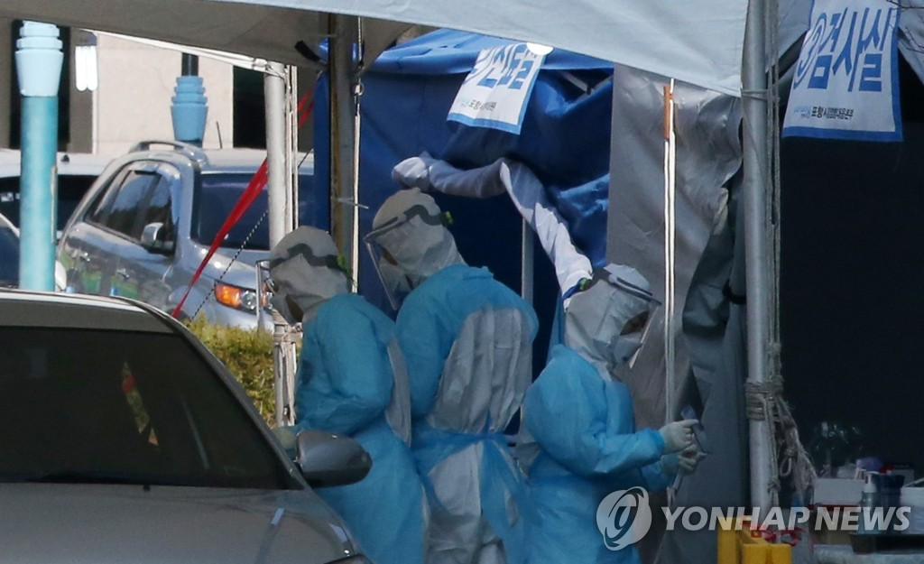 The photo taken on March 8, 2020, shows quarantine workers checking people for symptoms of the novel coronavirus at a drive-through diagnosis center in Pohang, located some 370 kilometers southeast of Seoul. (Yonhap)