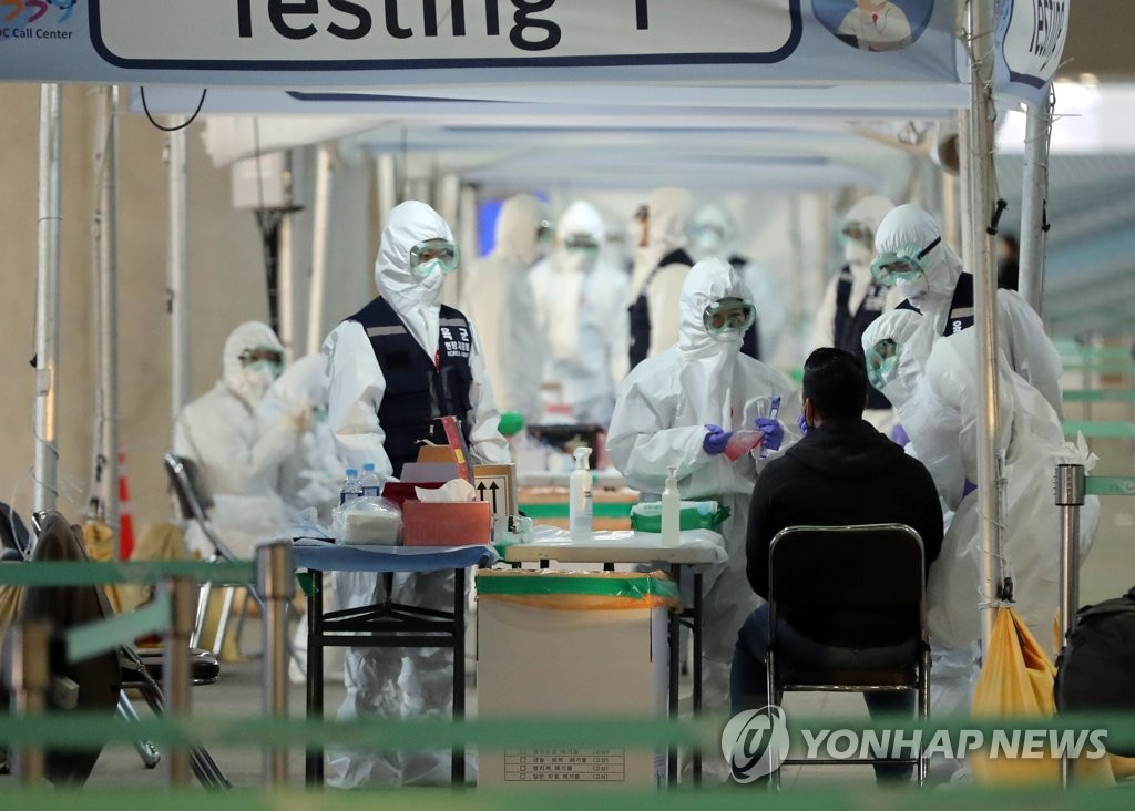 A passenger from the United States receives a test for the coronavirus at an outdoor facility at Incheon International Airport, west of Seoul, on March 27, 2020. (Yonhap)