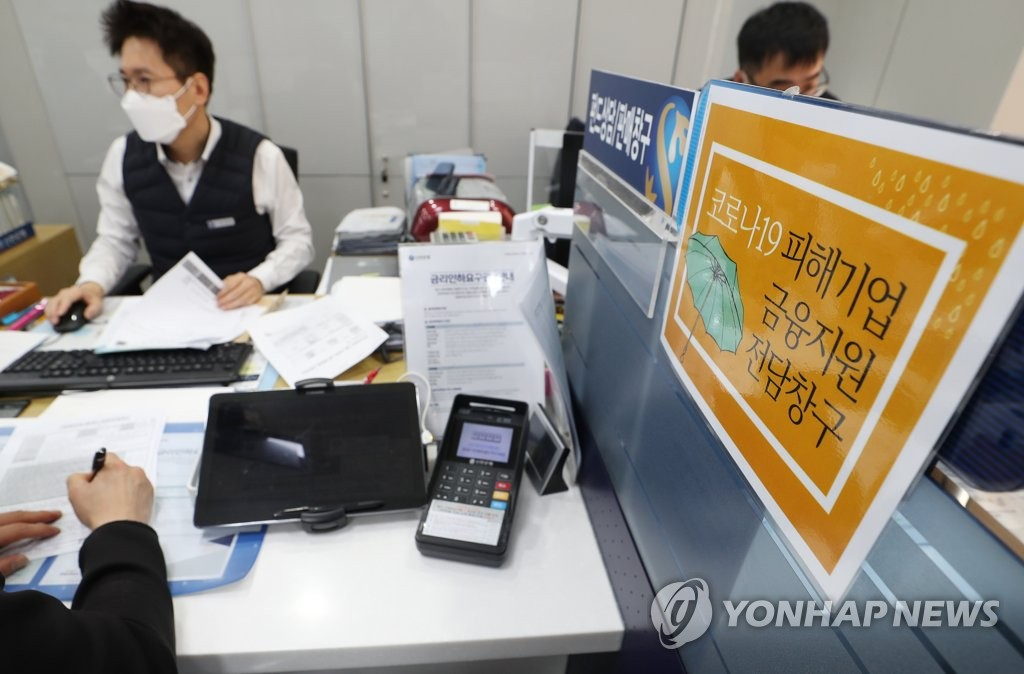 This file photo taken April 1, 2020, shows a merchant who suffered from the economic fallout of the new coronavirus outbreak appling for a loan at a Shinhan Bank branch in central Seoul. (Yonhap)