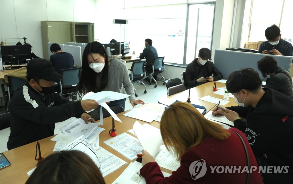 In the file photo, taken April 3, 2020, people are seen filling in application forms for special loans designed to support small businesses hit by the new coronavirus outbreak at a Seoul office of the Small Enterprise and Market Service. (Yonhap)
