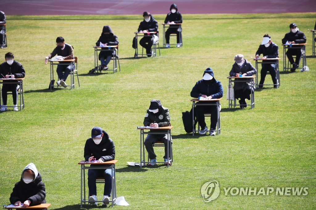 In this photo, taken April 4, 2020, job applicants are seen taking a test in an open field in Ansan, 40 kilometers south of Seoul, amid the government's social distancing campaign that strongly advises people to avoid crowds whenever possible. (Yonhap)