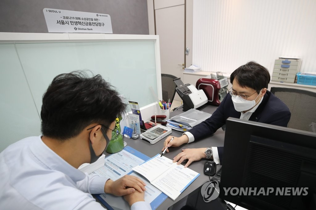 In this file photo, taken April 4, 2020, a bank official (R) at Shinhan Bank in Seoul explains a special low-interest rate product for small and medium-sized companies hit by the new coronavirus pandemic to a visiting customer. (Yonhap)