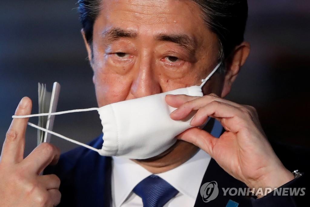 (도쿄 로이터=연합뉴스) 아베 신조 일본 총리가 6일 도쿄 총리관저에서 신종 코로나바이러스 감염증(코로나19) 확산을 막기 위한 긴급사태 선언 계획에 관해 설명하기 전에 마스크를 벗고 있다.