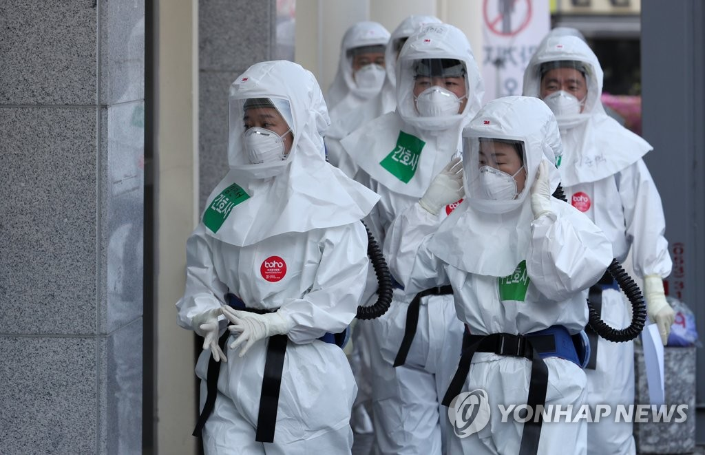 Health workers enter a hospital in Daegu to treat coronavirus patients on April 8, 2020. (Yonhap)