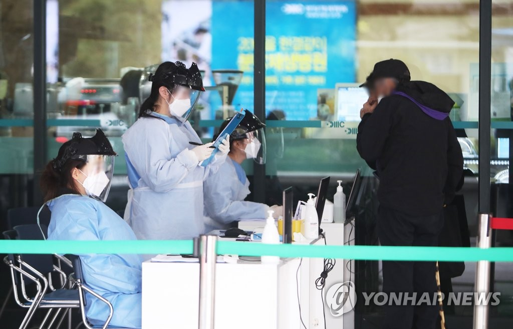 Medical workers check a visitor at Bundang Jesaeng Hospital in Seongnam, south of Seoul, on April 17, 2020. (Yonhap)