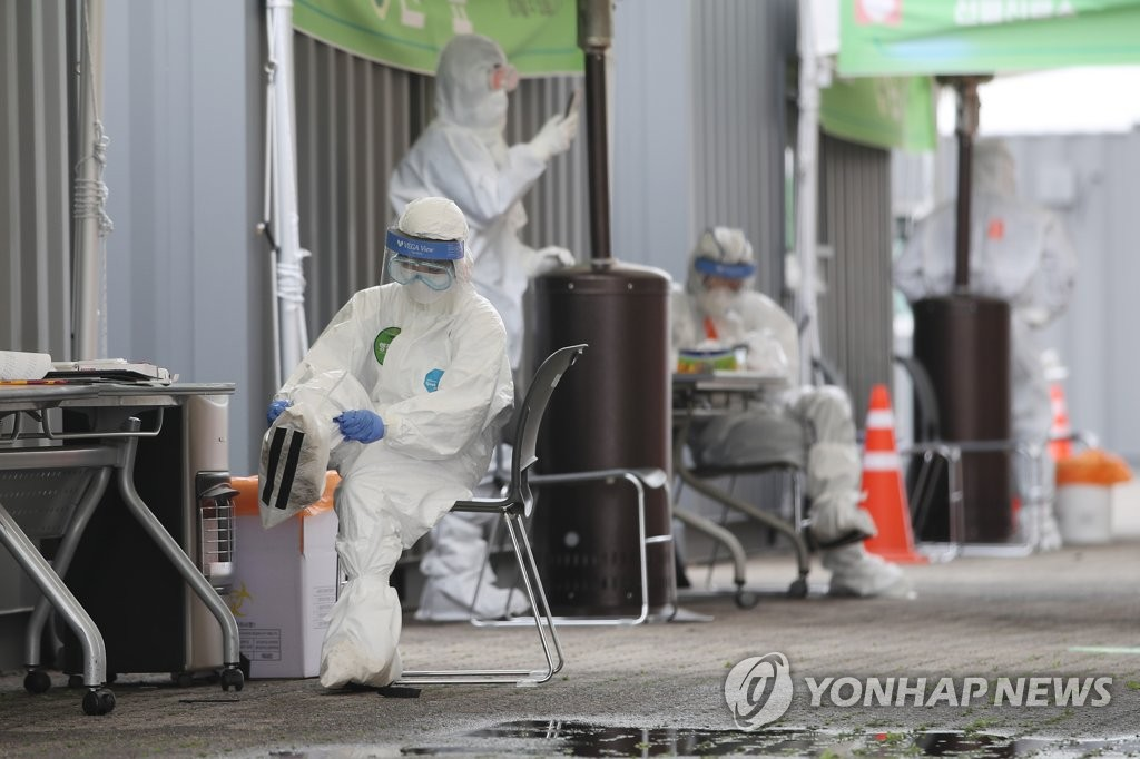 Medical workers get ready for work at a drive-thru test center in southern Seoul on April 20, 2020. (Yonhap)