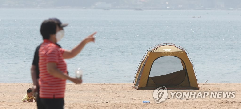 This photo, from May 6, 2020, shows mask-wearing pedestrians taking a walk at a beach in Changwon, 398 kilometers south of Seoul. (Yonhap)