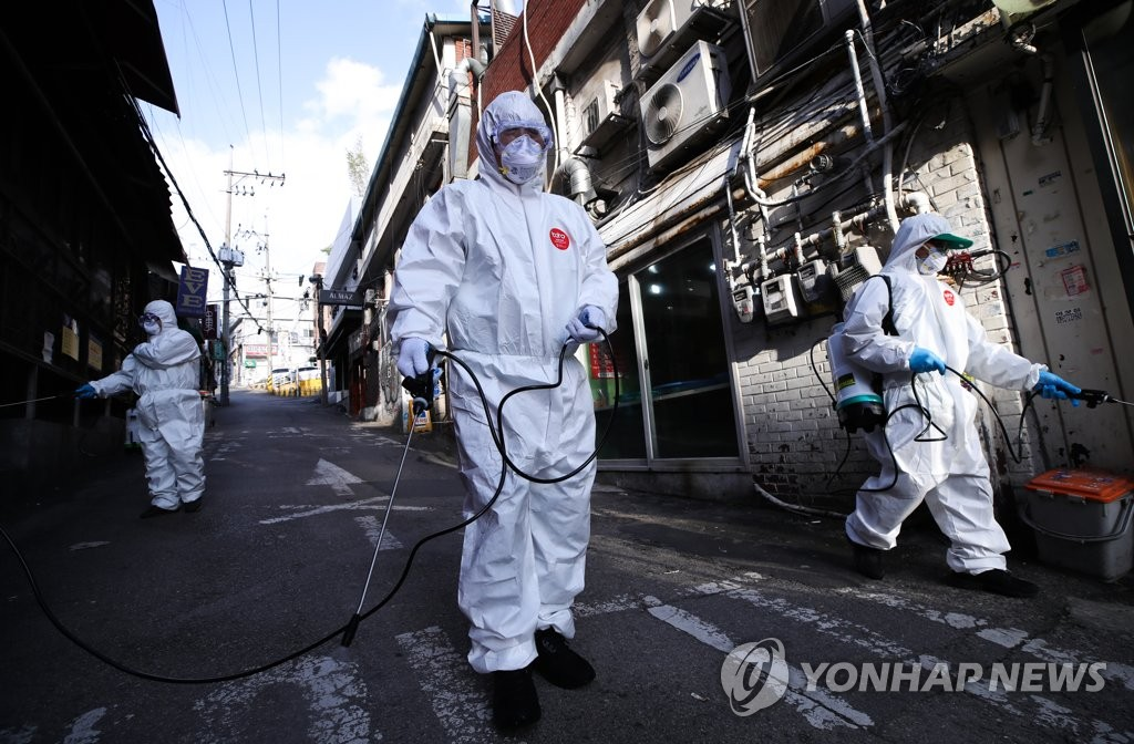 Volunteer workers disinfect a street in Itaewon located in the central Seoul ward of Yongsan on May 12, 2020. (Yonhap)