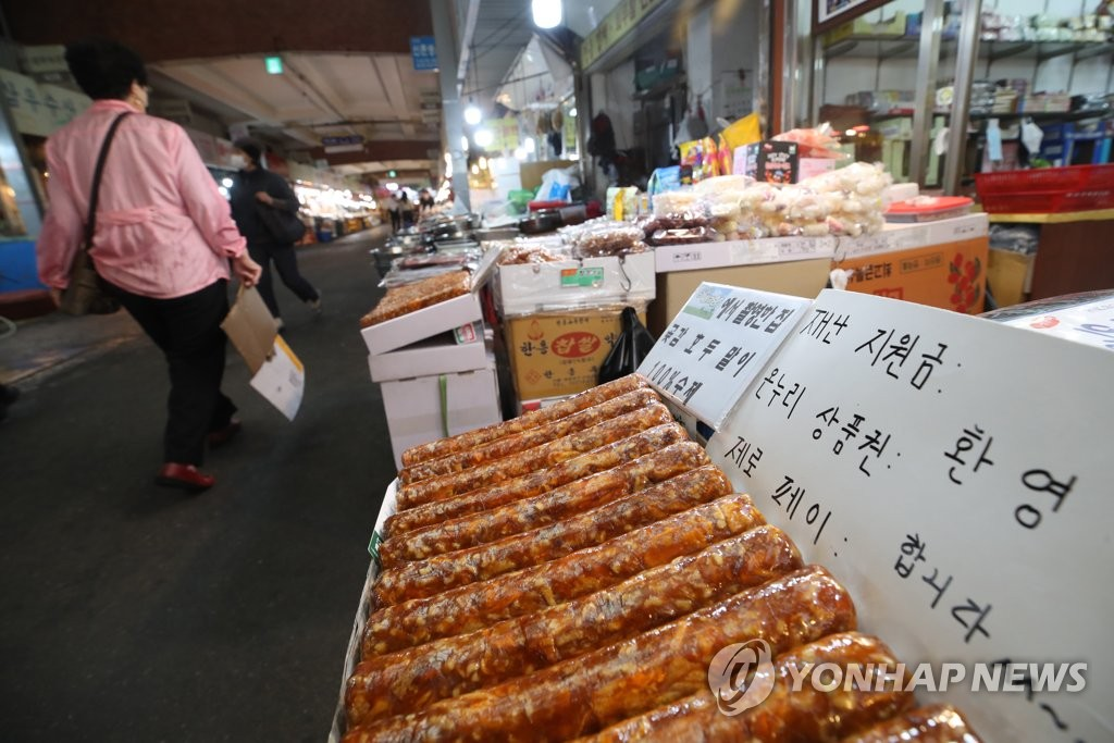 This May 19, 2020, photo shows a sign telling shoppers that they can pay with their emergency handout money at a traditional market in the central Seoul ward of Jongno. (Yonhap)