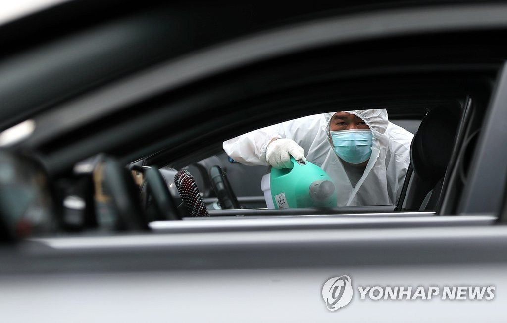 A worker disinfects a taxi in a parking lot in Incheon, west of Seoul, on May 22, 2020, to prevent the spread of the new coronavirus. (Yonhap)