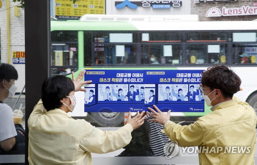 This photo, provided by the office of Gwangju Buk Ward on May 25, 2020, shows officials putting up notices about wearing face masks on public transportation at a bus stop near Chonnam National University in Gwangju. (Yonhap)