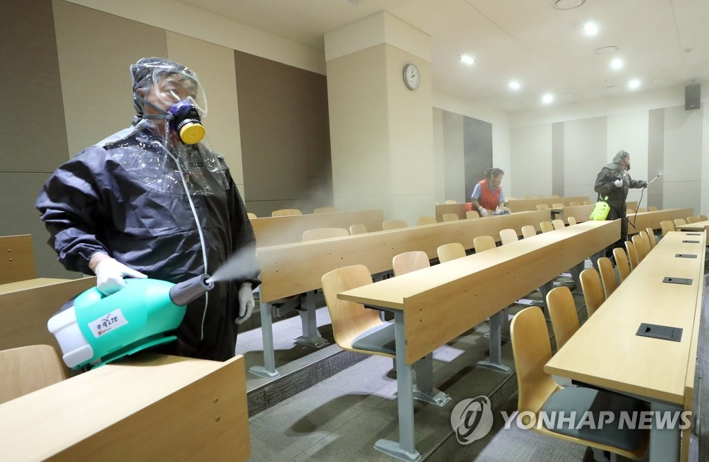 Sanitation staff members disinfect a classroom of Inha University in Incheon, west of Seoul, on June 11, 2020. (Yonhap)