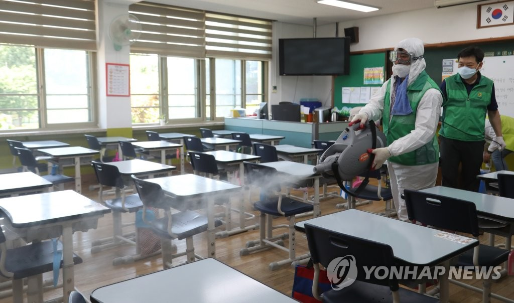 In this photo, taken on June 11, 2020, health workers disinfect a classroom at an elementary school in Seoul. (Yonhap)