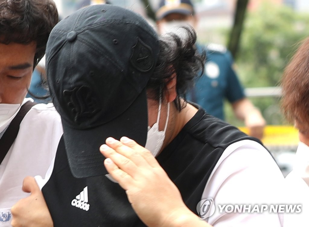 The police transfer a 35-year-old suspect accused of abusing his nine-year-old stepdaughter in the southeastern city of Changnyeong on June 13, 2020. (Yonhap)