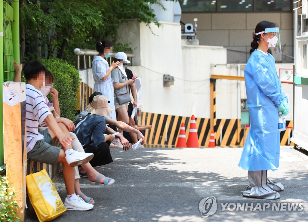 People wait in the shade to receive virus tests at a public medical center in Seoul on June 22, 2020. (Yonhap)