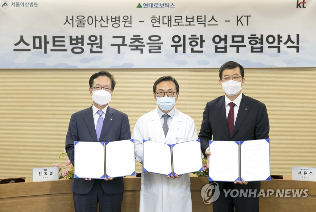 KT Vice President Jeon Hong-beom (L), Asan Medical Center President Lee Sang-do (C) and Hyundai Robotics CEO Seo Yoo-seong pose for a photo after signing an agreement to jointly develop smart medical services, in this photo provided by KT on July 1, 2020. (PHOTO NOT FOR SALE) (Yonhap)