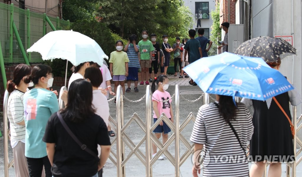 Students and parents wait in line to receive new coronavirus tests at an elementary school located north of Seoul on July 5, 2020. (Yonhap)