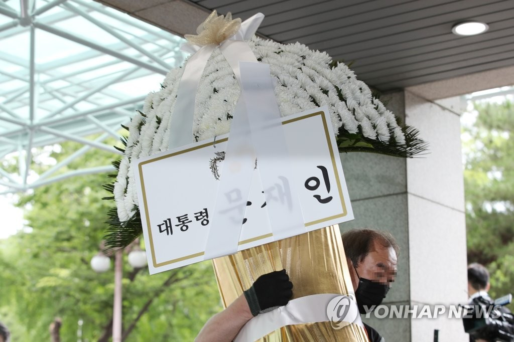 A delivery person carries condolence flowers sent by President Moon Jae-in to mourn the death of Seoul Mayor Park Won-soon at Seoul National University hospital on July 10, 2020. (Yonhap)