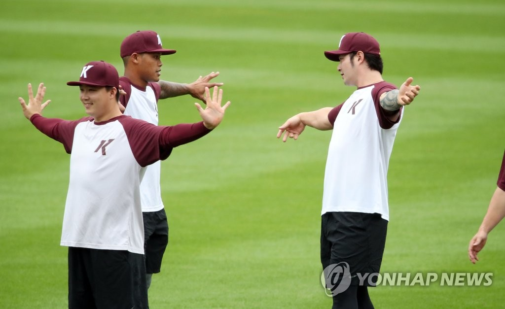 Addison Russell (C) and Park Byung-ho (R) of the Kiwoom Heroes (R) chat as they stretch ahead of a Korea Baseball Organization regular season game against the Doosan Bears at Jamsil Baseball Stadium in Seoul on July 28, 2020. (Yonhap)