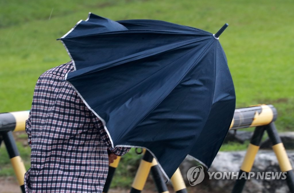 A pedestrian struggles to carry an umbrella as heavy rain fell at Haeundae Beach in the southeastern port city of Busan on Aug. 10, 2020, as Typhoon Jangmi moved northward. (Yonhap)