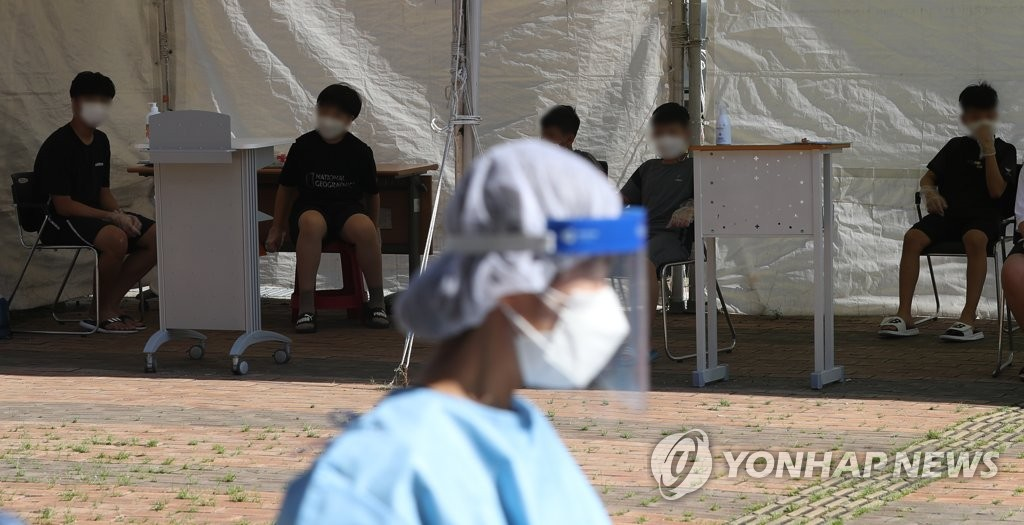 School children wait for new coronavirus tests in front of a South Korean health center, in this file photo. (Yonhap)