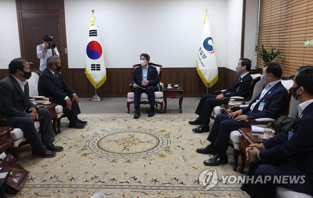 Unification Minister Lee In-young (C), South Korea's point man on inter-Korean relations, talks with a group of businesspeople who have factories in the suspended inter-Korean industrial park in the North Korean border town of Kaesong during their meeting at the government complex in Seoul on Aug. 21, 2020. (Yonhap)