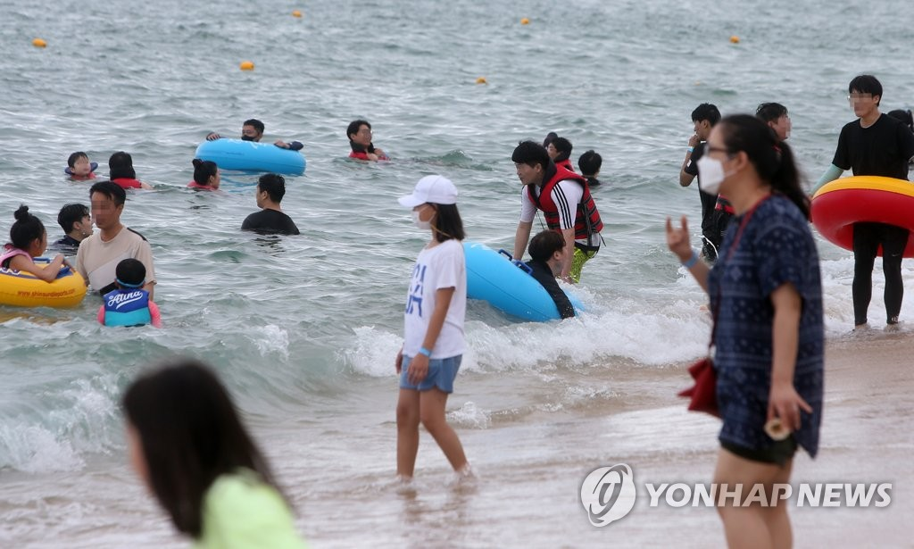 People swim at Gyeongpo Beach in Gangneung, Gangwon Province, on Aug. 22, 2020. All the beaches around the country will be closed from midnight Saturday due to the coronavirus pandemic. (Yonhap)