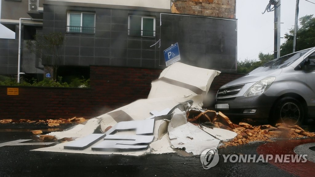 Parts of a building fell onto an outdoor parking lot on the southern resort island of Jeju due to Typhoon Bavi on Aug. 26, 2020. (Yonhap)