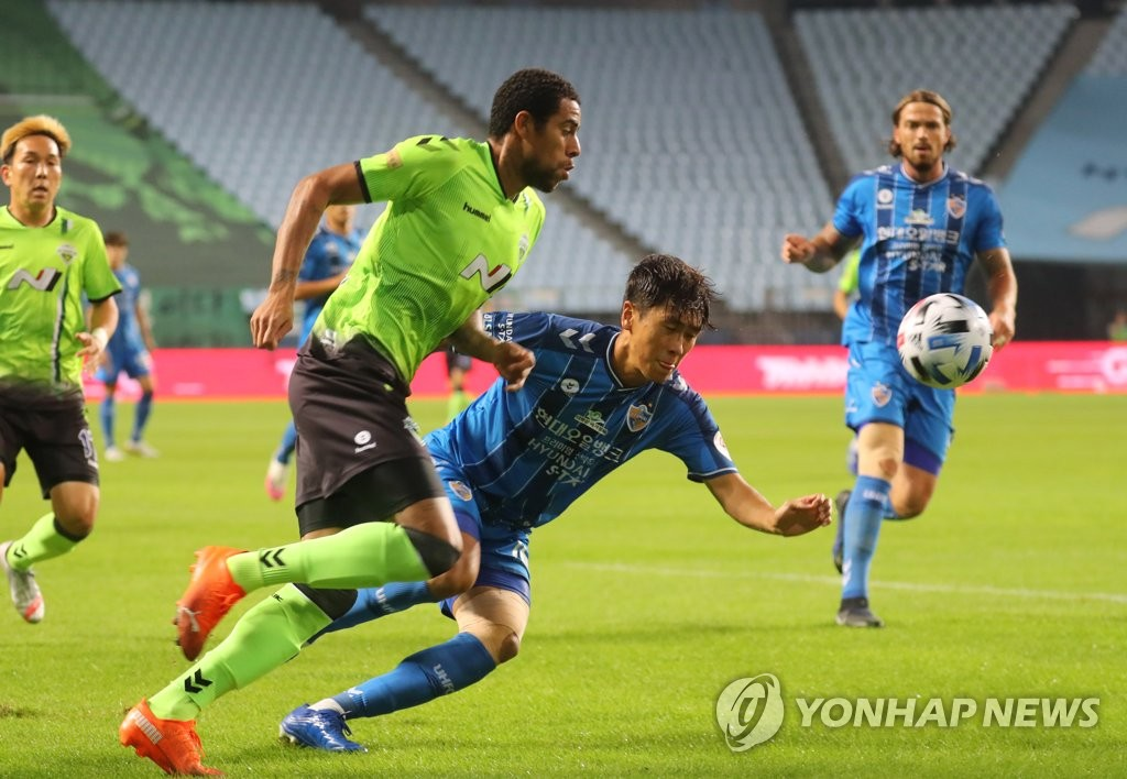 Gustavo of Jeonbuk Hyundai Motors (L) dribbles past Won Du-jae of Ulsan Hyundai FC during a K League 1 match at Jeonju World Cup Stadium in Jeonju, 240 kilometers south of Seoul, on Sept. 15, 2020. (Yonhap)
