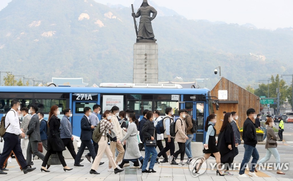 Pedestrians wearing protective masks walk around central Seoul on Oct. 12, 2020. (Yonhap)
