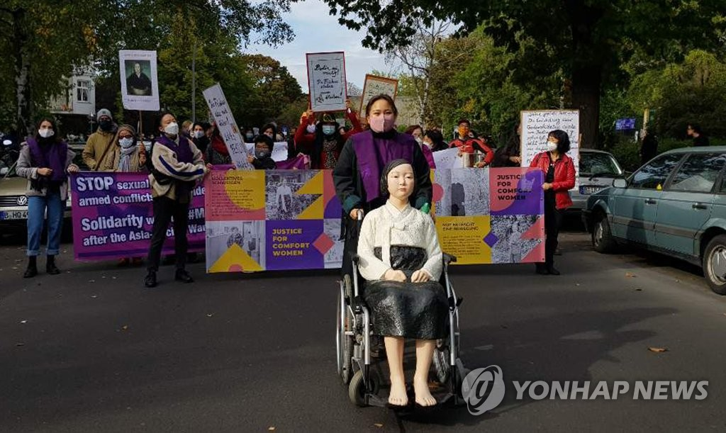 Activists and citizens march in Berlin on Oct. 13, 2020, calling for the withdrawal of a district office's order to remove the Statue of Peace, which symbolizes Korean victims of Japan's wartime sexual slavery. (Yonhap)