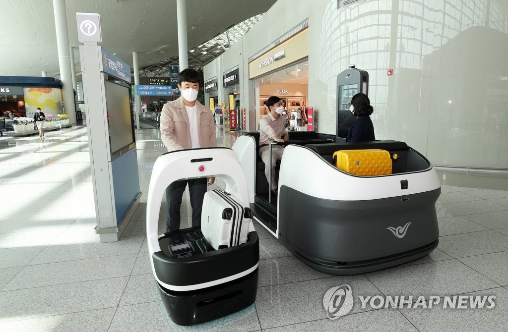 This photo, provided by Incheon International Airport Corp. (IIAC), shows IIAC officials test-running a self-driving vehicle (R) and an autonomous cart robot in the departure lobby of the airport's second terminal on Oct. 14, 2020. (PHOTO NOT FOR SALE) (Yonhap)
