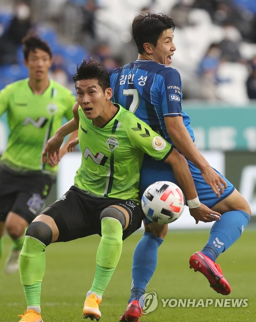 In this file photo from Oct. 25, 2020, Lee Yong of Jeonbuk Hyundai Motors (L) battles Kim In-sung of Ulsan Hyundai FC for the ball during a K League 1 match at Ulsan Munsu Football Stadium in Ulsan, 415 kilometers southeast of Seoul. (Yonhap)