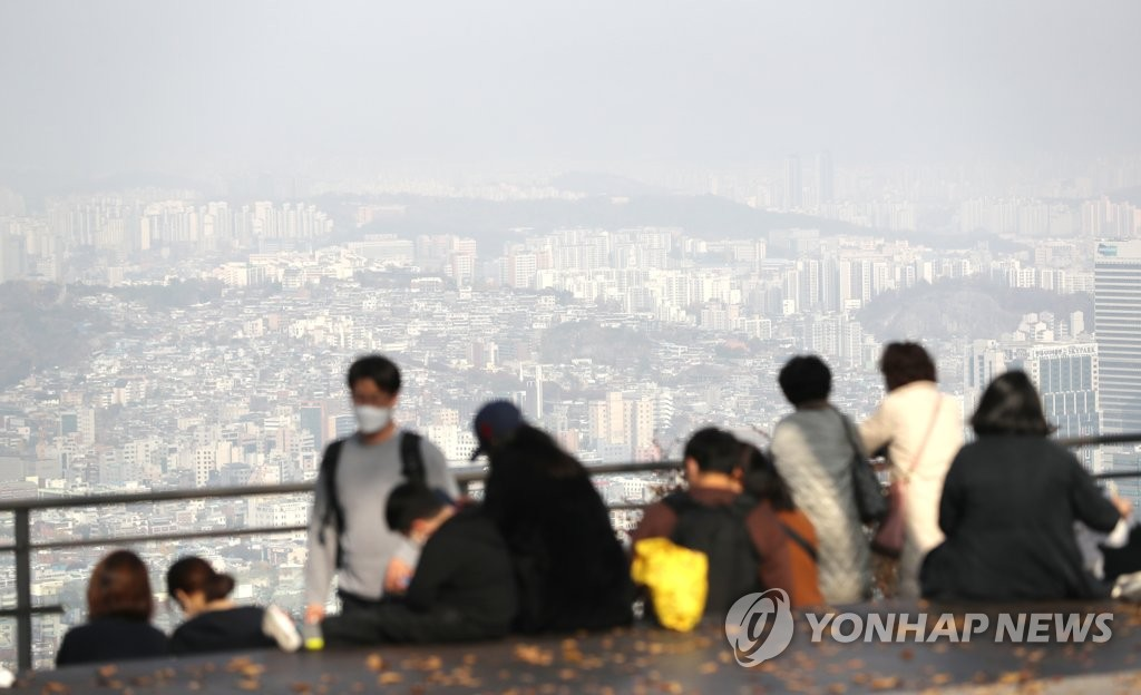 People wearing protective masks walk around a park in central Seoul on Nov. 7, 2020. (Yonhap)