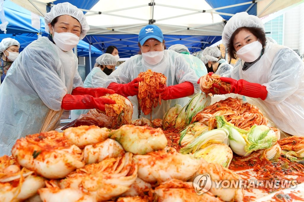 A group of volunteers poses with kimchi, a traditional Korean side dish normally made of fermented cabbage, salt and hot peppers, during an event held in eastern Seoul on Nov. 18, 2020, in this photo released by the Seongdong Ward. (PHOTO NOT FOR SALE) (Yonhap)