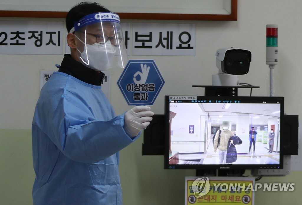 A teacher in protective gear checks students' body temperatures at a high school in Masan, South Gyeongsang Province, on Dec. 3, 2020, before the nationwide college entrance exam begins. (Yonhap)