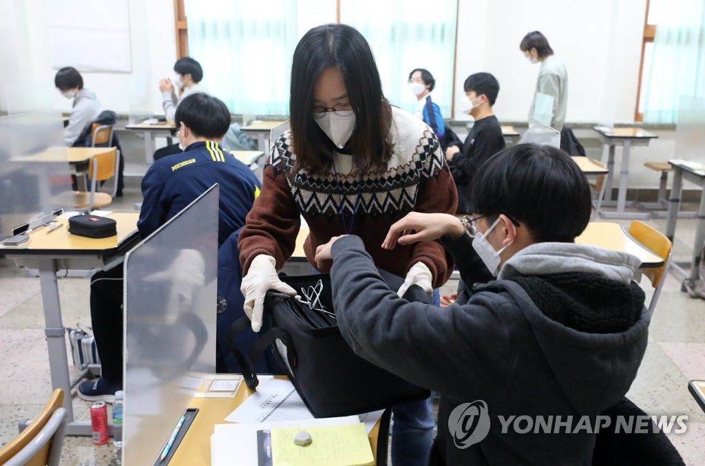 A proctor collects test takers' belongings at a high school in Seoul on Dec. 3, 2020, before the college entrance exam begins. (Pool photo) (Yonhap)