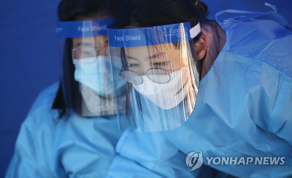 Officials prepare to carry out COVID-19 tests at a makeshift clinic in central Seoul on Dec. 14, 2020. (Yonhap)