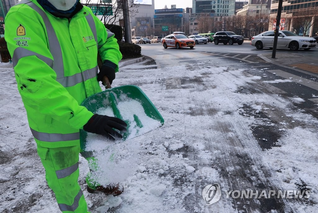A Jongno Ward worker sprays calcium chloride on pedestrian paths in the district in Seoul on Jan. 12, 2021. (Yonhap)