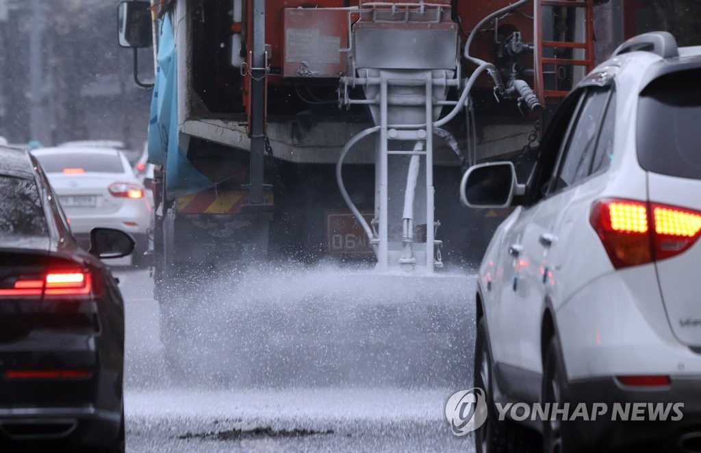 A snowplow sprays calcium chloride on roads amid snowfall in Seoul's central Jongno Ward on Jan. 12, 2021. (Yonhap)