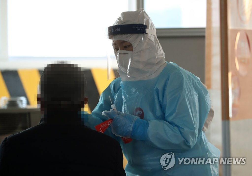 This photo taken on Jan. 20, 2021, shows a health worker clad in protective suit collecting a sample from a citizen at a makeshift virus testing clinic in the southwestern city of Gwangju. (Yonhap)