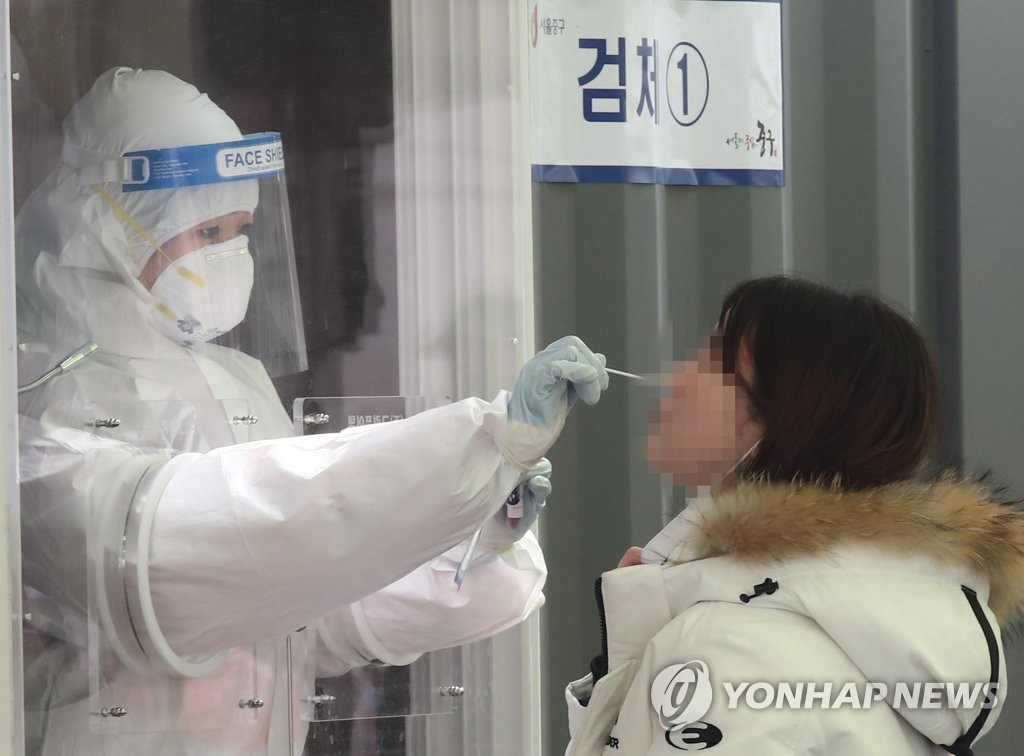 A medical worker conducts a COVID-19 test on a woman at a screening station in front of Seoul Station on Feb. 15, 2021. (Yonhap)