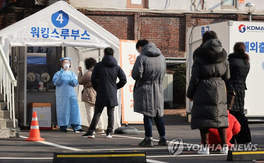 Citizens wait in line to receive COVID-19 tests at a testing site of the National Medical Center in central Seoul on Feb. 21, 2021. (Yonhap)