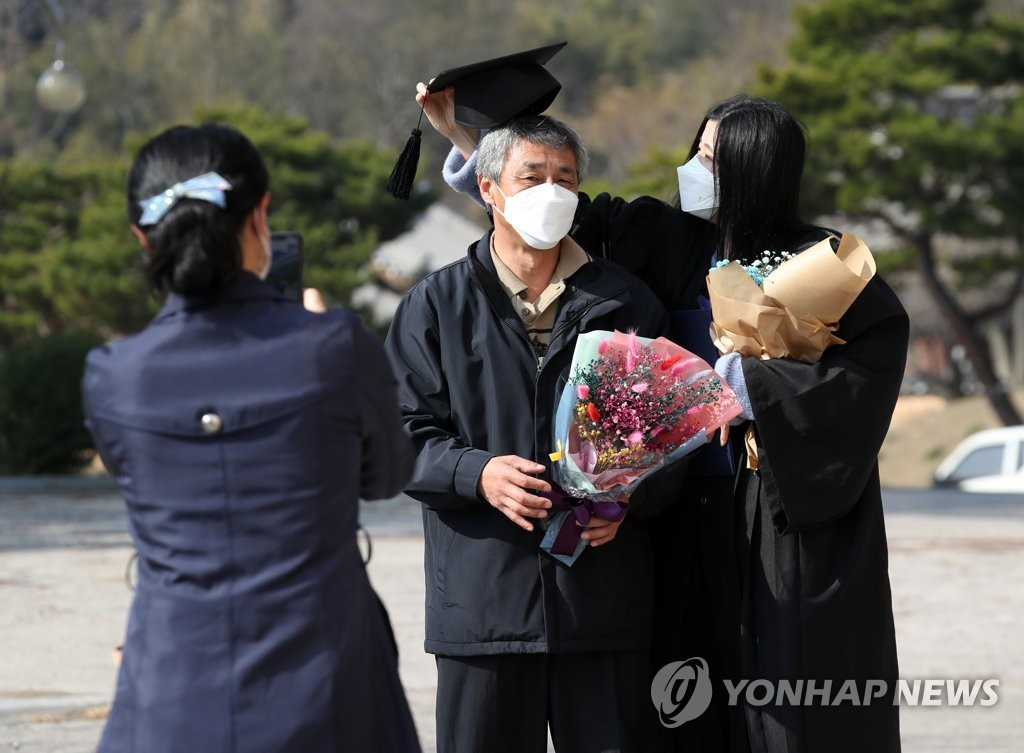 A family wearing protective masks takes a photo during a graduation ceremony held at Dongshin University in Naju, 355 kilometers south of Seoul, on Feb. 22, 2021. (Yonhap)